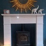 """After, limestone fire surround with stovax wood burner fitted, sunburst mirror adds a little 70's vibe"""